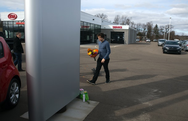 KALAMAZOO, MI - FEBRUARY 21: A man places flowers at Kia Dealship where a gunman went on a shooting rampage on February 21, 2016 in Kalamazoo, Michigan. Authorities said that a shooter who killed six people and injured two others was an Uber driver who appears to have gunned down people at random during a  four-hour rampage in the parking lots of a western Michigan apartment complex, a car dealeship and a Cracker Barrel store.  (Photo by Tasos Katopodis/Getty Images)