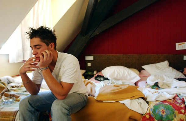 STRASBOURG, FRANCE - MAY 18: Cocchi Andrea, 20, an Italian student from the Primo Levi Technical Institute of Vignola in the Modena Province, smokes a cigarette as he sits on his hotel bed during a school trip to Strasbourg, France to visit the European Parliament May 18, 2004. STRASBOURG, FRANCE - MAY 18: Juri Lolli, 19, (L) and Diego Malagoli, 20, (R) Italian students from the Primo Levi Technical Institute of Vignola in the Modena Province, watch as another friends buys a g-string for his girlfriend in a department store during a school trip to Strasbourg to visit the European Parliament May 18, 2004. School trips can be a sort of initiation trip for teenagers, where they are introduced for the first time to alcohol and drugs. Many times they don't sleep for the whole trip. The trips often allow the students to get to know each other better. If one is considered 'different' than the group, it can be a nightmare experience for the teenager. Mainly the teenagers are only interested in clubs, shopping and having a pizza instead of the cultural aspects of the school trip. (Photo by Marco Di Lauro/Getty Images)