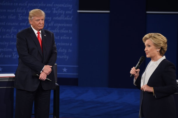 US Republican presidential candidate Donald Trump (L) listens to US Democratic presidential candidate Hillary Clinton during the second presidential debate at Washington University in St. Louis, Missouri, on October 9, 2016. / AFP / Robyn Beck        (Photo credit should read ROBYN BECK/AFP/Getty Images)