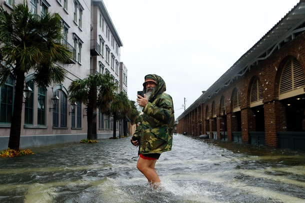 CHARLESTON, SC - OCTOBER 8:  Local tour guide Larry Gerald live streams himself on social media as he crosses flooded S. Market Street at East Bay St. in the wake of Hurricane Matthew on October 8, 2016 in Charleston, South Carolina. Across the Southeast, Over 1.4 million people have lost power due to Hurricane Matthew which has been downgraded to a category 1 hurricane on Saturday morning. (Photo by Brian Blanco/Getty Images)