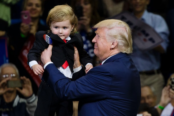 Republican presidential nominee Donald Trump holds as child dressed as him during a rally at Mohegan Sun Arena in Wilkes-Barre, Pennsylvania on October 10, 2016. / AFP / DOMINICK REUTER        (Photo credit should read DOMINICK REUTER/AFP/Getty Images)