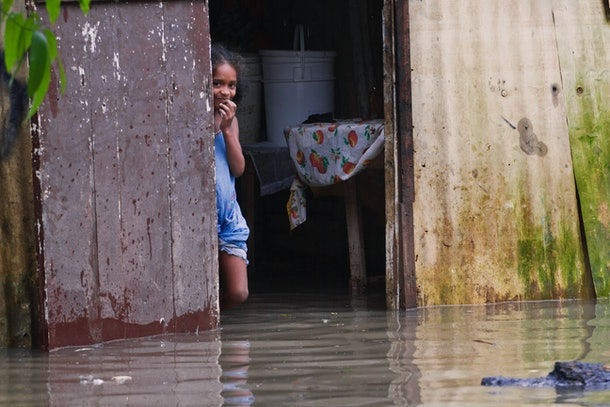 A child observes from her flooded house at La Barquita neighborhood, eastern Santo Domingo on October 25, 2012. Hurricane Sandy barreled toward the Bahamas Thursday as a powerful category two storm, after battering Jamaica, Haiti and Cuba and claiming three lives so far. The US-based National Hurricane Center said the storm was packing winds of up to 105 miles (165 kilometers) per hour as it moved north, near the top of the category two range on the five-rung Saffir-Simpson wind scale. Forecasters predicted the storm would weaken somewhat over the next 48 hours. But Sandy will remain a hurricane as it passes over the Bahamas, according to the NHC's 1500 GMT advisory. AFP PHOTO/ERIKA SANTELICES        (Photo credit should read ERIKA SANTELICES/AFP/Getty Images)