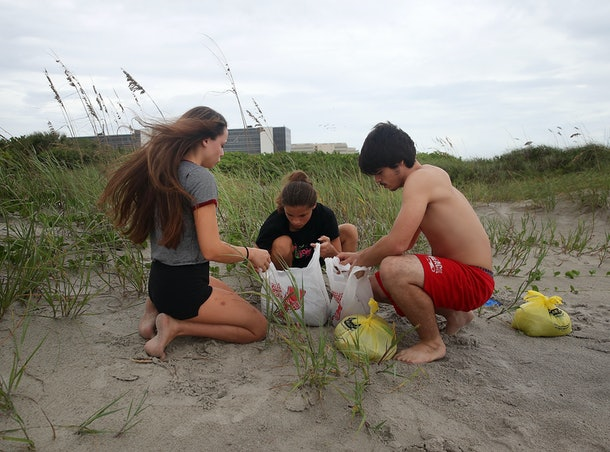 COCOA, FL - OCTOBER 06: Brother and sisters, Nicholas, (R), Jasmine, (C), and Samantha Cleveland (L), put sand in plastic shopping bags to be placed at their home nearby as Hurricane Matthew approaches, October 6, 2016 on Cocoa Beach, Florida. Hurricane Matthew is expected to reach the area later this afternoon bringing heavy wind, and widespread flooding.  (Photo by Mark Wilson/Getty Images)