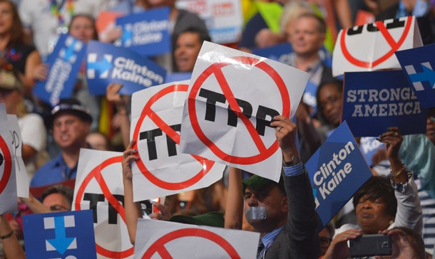 People hold signs against the Trans Pacific Partnership (TPP) on  Day 3 of the Democratic National Convention at the Wells Fargo Center, July 27, 2016 in Philadelphia, Pennsylvania.      / AFP / Mandel Ngan        (Photo credit should read MANDEL NGAN/AFP/Getty Images)