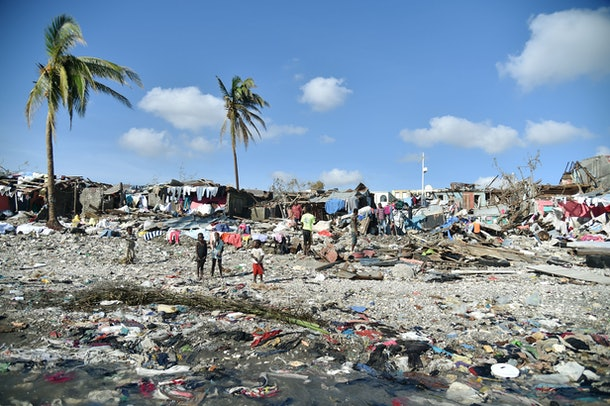 Haitians walk the site ofdestroyed houses and debris left by  Hurricane Matthew in Jeremie, Haiti, on October 8, 2016.  The full scale of the devastation in hurricane-hit rural Haiti became clear Saturday as the death toll surged past 400, three days after Matthew leveled huge swaths of the country's south. / AFP / HECTOR RETAMAL        (Photo credit should read HECTOR RETAMAL/AFP/Getty Images)