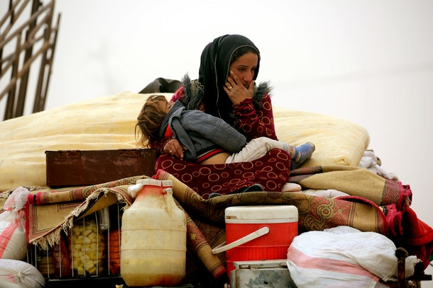 TOPSHOT - A Syrian woman carries her child at a temporary refugee camp in the village of Ain Issa, housing people who fled Islamic State group's Syrian stronghold Raqa, some 50 kilometres (30 miles) north of the group's de facto capital on November 10, 2016. The US-backed Syrian Democratic Forces (SDF) said their advance on Raqa was being held back by a sandstorm that had hit the desert province. Speaking in Ain Issa, the main staging point for the operation some 50 kilometres (30 miles) north of Raqa, the commander said the sandstorm was also impeding visibility for coalition warplanes.  / AFP / DELIL SOULEIMAN        (Photo credit should read DELIL SOULEIMAN/AFP/Getty Images)