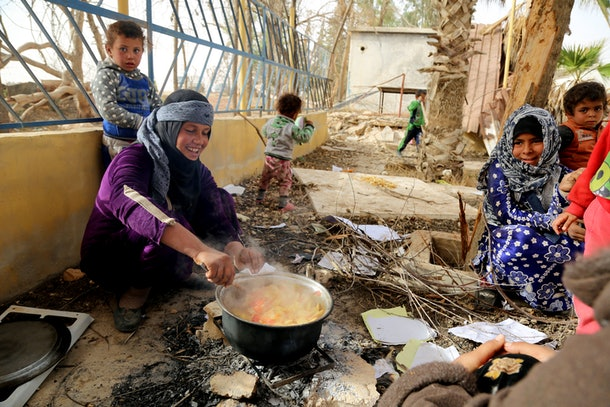 A Syrian woman cooks potatoes for her children at a temporary refugee camp in the village of Ain Issa, housing people who fled Islamic State group's Syrian stronghold Raqa, some 50 kilometres (30 miles) north of the group's de facto capital on November 10, 2016. The US-backed Syrian Democratic Forces (SDF) said their advance on Raqa was being held back by a sandstorm that had hit the desert province. Speaking in Ain Issa, the main staging point for the operation some 50 kilometres (30 miles) north of Raqa, the commander said the sandstorm was also impeding visibility for coalition warplanes.  / AFP / DELIL SOULEIMAN        (Photo credit should read DELIL SOULEIMAN/AFP/Getty Images)