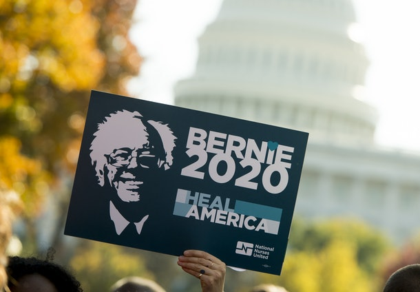 A supporter of US Senator Bernie Sanders(I-VT), holds up a 'Bernie 2020' sign as he speaks during a rally to stop the Trans-Pacific Partnership (TPP) organized by National Nurses United and the People for Bernie Sanders, on Capitol Hill in Washington, DC, November 17, 2016. / AFP / SAUL LOEB        (Photo credit should read SAUL LOEB/AFP/Getty Images)