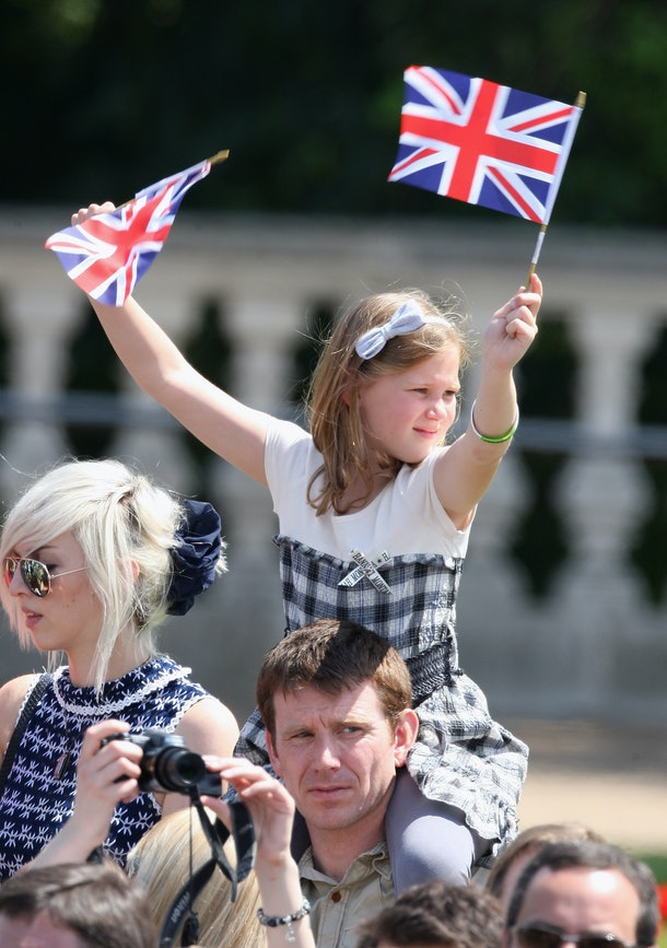 LONDON, ENGLAND - JUNE 13:  A girl in the crowd waves Union Jacks as the Royal Party arrives back at Buckingham Palace in a horse drawn carriages after the Trooping the Colour ceremony on June 13, 2009 in London, England. The ceremony of Trooping the Colour is believed to have first been performed during the reign of King Charles II. In 1748, it was decided that the  parade would be used to mark the official birthday of the Sovereign. More than 600 guardsmen and cavalry make up the parade, a celebration of the Sovereign's official birthday, although the Queen's actual birthday is on 21 April.  (Photo by Chris Jackson/Getty Images)