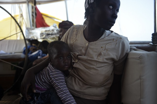 A mother holds her child after migrants were rescued by members of Proactiva Open Arms NGO in the Mediterranean Sea, some 12 nautical miles north of Libya, on October 4, 2016. At least 1,800 migrants were rescued off the Libyan coast, the Italian coastguard announced, adding that similar operations were underway around 15 other overloaded vessels. / AFP / ARIS MESSINIS        (Photo credit should read ARIS MESSINIS/AFP/Getty Images)