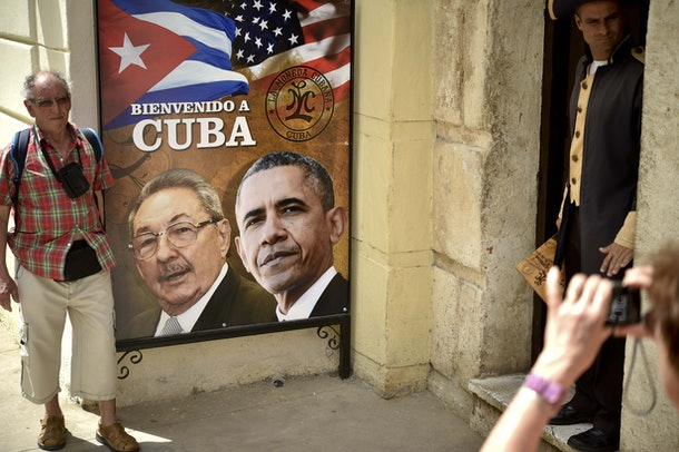 A tourist poses for a picture with a sign placed at the entrance of a restaurant with the images of Cuban and US Presidents Raul Castro and Barack Obama in Havana, Cuba on March 19, 2016. Political and economic reforms in Cuba will be a no-go area during talks between Cuban leader Raul Castro and US President Barack Obama, Cuban Foreign Minister Bruno Rodriguez said in Havana Thursday. On Sunday, Obama will become the first sitting US president to visit Cuba since 1928, capping his historic policy of ending a bitter standoff that has endured since Fidel Castro's overthrow of the US-backed government of Fulgencio Batista in 1959.  AFP PHOTO/ Yuri CORTEZ / AFP / YURI CORTEZ        (Photo credit should read YURI CORTEZ/AFP/Getty Images)