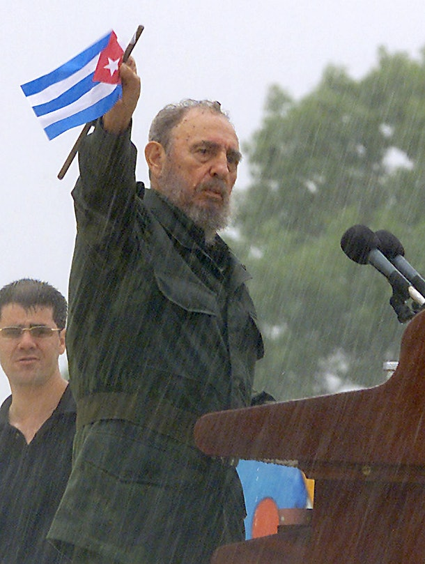 Cuban president Fidel Castro waves the Cuban flag in the rain, during a speech, 01 June 2002, in Holguín, about 500 miles east of Havana. Castro affirmed, 01 June 2002, before more than 400,000 Cubans and in the middle of an intense rain that the socialist course of its regime will maintain without changes, in spite of the calls of Washington for change.                    AFP PHOTO/Adalberto ROQUE / AFP / ADALBERTO ROQUE        (Photo credit should read ADALBERTO ROQUE/AFP/Getty Images)