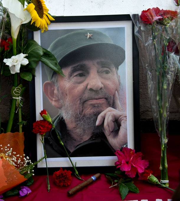 A portrait of Cuban historic revolutioonary leader Fidel Castro is surrounded by flowers as people gather outside the Cuban embassy in Santiago on November 26, 2016, the day after he died aged 90.  One of the world's longest-serving rulers and modern history's most singular characters, Castro defied 11 US administrations and hundreds of assassination attempts. / AFP / MARTIN BERNETTI        (Photo credit should read MARTIN BERNETTI/AFP/Getty Images)