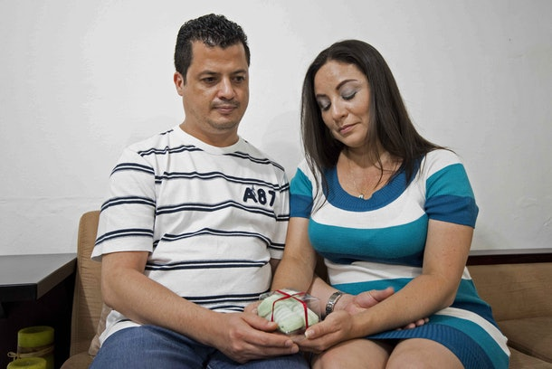 Evelyn Espinoza (R) and her husband Esteban Chacon (L) hold bootees at their home in Alajuelita, 10 km south of San Jose, Costa Rica on September 30, 2015, as they wait for an in vitro fertilization  (IVF) treatment. Past September 10 the Costa Rican government issued a decree legalizing IVF, which was banned 15 years ago by the Constitutional Chamber of the Supreme Court of Justice.  AFP PHOTO / Ezequiel BECERRA        (Photo credit should read EZEQUIEL BECERRA/AFP/Getty Images)