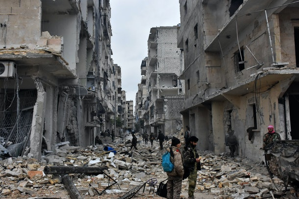 TOPSHOT - Syrian pro-government forces advance in the Jisr al-Haj neighbourhood during the ongoing military operation to retake remaining rebel-held areas in the northern embattled city of Aleppo on December 14, 2016.  Shelling and air strikes sent terrified residents running through the streets of Aleppo as a deal to evacuate rebel districts of the city was in danger of falling apart.