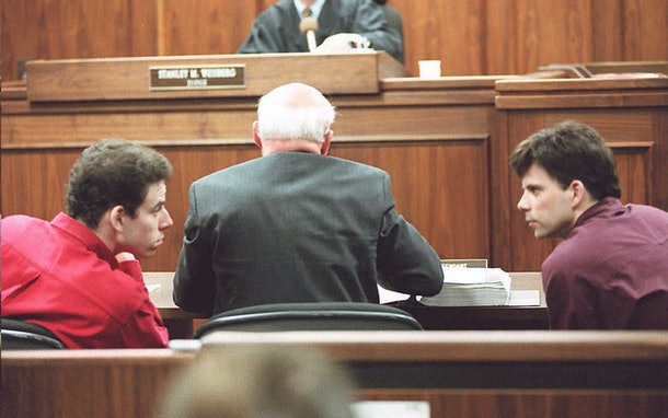 LOS ANGELES, UNITED STATES:  Erik (L) and Lyle (R) Menendez converse in the courtroom during a hearing in Los Angeles, in this 02 February 1995 file picture. They are accused of murdering their parents in 1989. (Photo credit should read