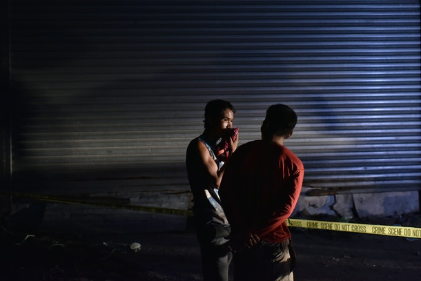 PASAY CITY, PHILIPPINES - NOVEMBER 17: Curious passersby view a crime scene where two unidentified male victims were found on a dark alley on November 17, 2016 in Pasay city, Philippines. Metro police noticed a rising number of summary execution tyoe of killings were victims are abducted, killed, and with faces wrapped in tape. Filipino residents fear a rising wave of violence as President Rodrigo Duterte's war on drugs continues after almost six months and has killed over 5,000 Filipinos since the crackdown, including police, users and dealers involved in drugs. Duterte's drug crackdown, which began in July 1, has been met with wide criticism from international organizations, including human rights group and the Obama administration as U.S. officials expressed deep concerns by reports of extrajudicial killings as he vowed to kill as many as 100,000 drug users and handlers back during his presidential campaign.  (Photo by Jes Aznar/Getty Images)