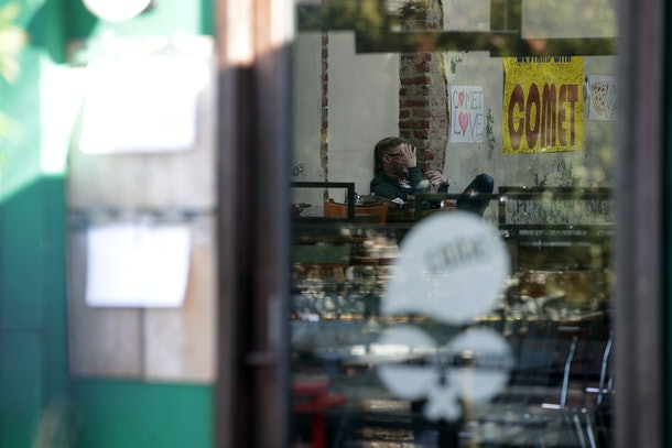 WASHINGTON, DC - DECEMBER 05:  A man sits inside Comet Ping Pong pizzeria as he talks on his phone December 5, 2016 in Washington, DC. A man was arrested Sunday after walking into the pizzeria and discharging a rifle, claiming he was 'self-investigating' an online conspiracy theory about a pedophilia ring being run by high-ranking Democrats, including Hillary Clinton.  (Photo by Alex Wong/Getty Images)