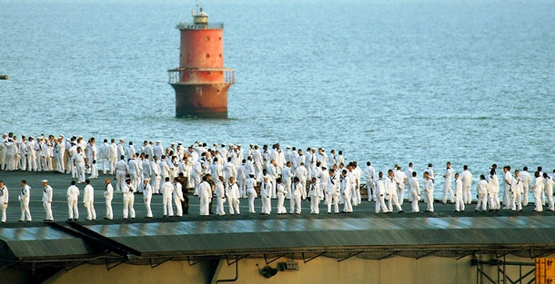 NORFOLK, VA - AUGUST 15:  Sailors on board the USS John F. Kennedy prepare to man the rail as the ship passes by the Hampton Roads Tunnel on its way to Naval Station Norfolk August 15, 2002 near Norfolk, Virginia. The Kennedy will station in Norfolk to drop off locally stationed squadron personnel before continuing its journey to its homeport of Mayport, Florida. The carrier just completed a six-month deployment to the Mediterranean Sea and the Arabian Gulf in support of Operation Enduring Freedom.  (Photo by Martin Maddock/U.S. Navy/Getty Images)