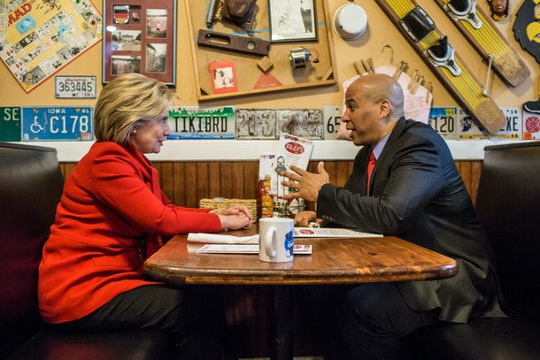 CEDAR RAPIDS, IOWA - JANUARY 24: Democratic presidential candidate Hillary Clinton (L) talks with Sen. Cory Booker (D-NJ) at Riley's Cafe on January 24, 2016 in Cedar Rapids, Iowa. The Democratic and Republican Iowa Caucuses, the first step in nominating a presidential candidate from each party, will take place on February 1. (Photo by Brendan Hoffman/Getty Images)