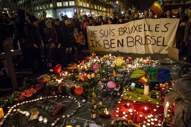 People hold a banner reading in French and Flamish 'I AM BRUSSELS' as they gather around floral tributes, candles, belgian and peace flags and notes in front of the Bourse of Brussels on March 22, 2016  in tribute to the victims of Brussels following triple bomb attacks in the Belgian capital that killed about 35 people and left more than 200 people wounded.  Belgium launched a huge manhunt on March 22 after a series of bombings claimed by the Islamic State group ripped through Brussels airport and a metro train, killing around 35 people in the latest attack to bring carnage to the heart of Europe.  / AFP / BELGA AND Belga / Aurore Belot / Belgium OUT        (Photo credit should read AURORE BELOT/AFP/Getty Images)