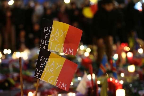 Belgian flags reading 'Pray for Belgium' are pictured as people gather at a makeshift memorial on the Place de la Bourse (Beursplein) in Brussels on March 23, 2016, a day after a triple bomb attack, which responsibility was claimed by the Islamic State group, left 31 dead and hundreds injured in the Belgian capital. World leaders united in condemning the carnage in Brussels and vowed to combat terrorism, after Islamic State bombers killed 31 people in a strike at the symbolic heart of the EU. AFP PHOTO / KENZO TRIBOUILLARD / AFP / KENZO TRIBOUILLARD        (Photo credit should read KENZO TRIBOUILLARD/AFP/Getty Images)