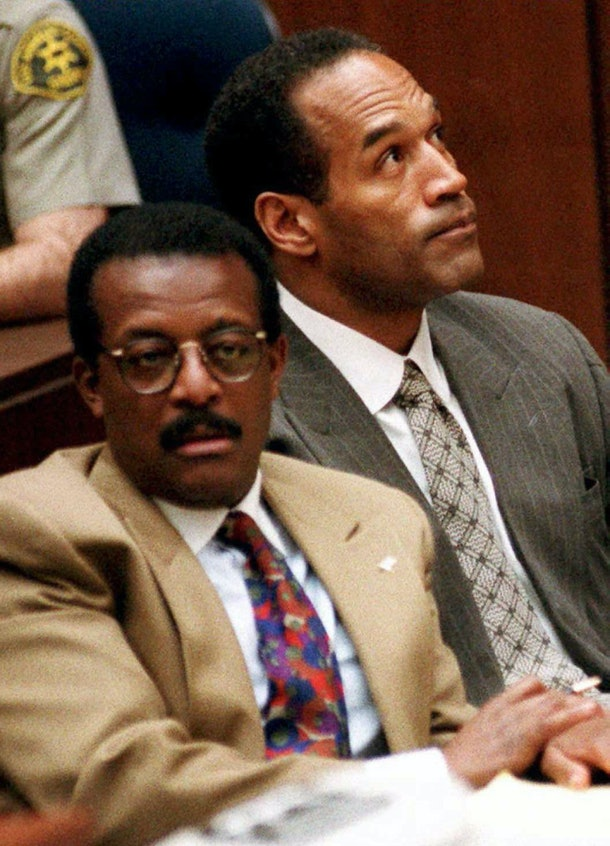 LOS ANGELES, CA - FEBRUARY 3:  O.J. Simpson (R) reacts as he and attorney Johnnie Cochran Jr. listen during his murder trial 03 February in Los Angeles to testimony of Denise Brown, sister of Simpson's ex-wife Nicole Brown Simpson. (COLOR KEY: Cochran's ties has red, blue and green.)  (Photo credit should read POO/AFP/Getty Images)