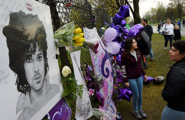 Prince fans beside a sea of purple balloons and flowers at a memorial wall outside the Paisley Park compound of music legend Prince who died suddenly at the age of 57 in Minneapolis, Minnesota, on April 24, 2016. His death came just a week after the enigmatic Grammy and Oscar winner -- acclaimed for his guitar skills and soaring falsetto -- was taken to a hospital with a flu-like illness that he later made light of. / AFP / Mark Ralston        (Photo credit should read MARK RALSTON/AFP/Getty Images)