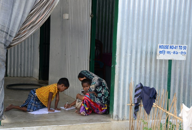 New Indian citizens study with the help of their mother at Dinhata Enclave settlement camp in Cooch Behar district on May 4, 2016, on the eve of voting in the final phase of state assembly elections in the eastern Indian state of West Bengal.  The family are among many who became Indian citizens after a transfer of enclaves between India and Bangladesh in 2015, when India and Bangladesh signed a Land Boundary Agreement. Under the agreement Bangladesh had transferred 51 enclaves to India while India transferred 111 to Bangladesh.  / AFP / DIPTENDU DUTTA        (Photo credit should read DIPTENDU DUTTA/AFP/Getty Images)