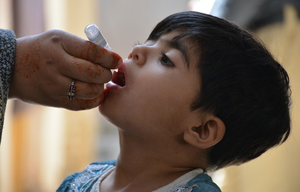 A Pakistani health worker administers polio drops to a child during a polio vaccination campaign in Quetta on April 26, 2016. Islamist outfits including the Pakistani Taliban say the polio vaccination drive is a front for espionage or a conspiracy to sterilise Muslims. / AFP / BANARAS KHAN        (Photo credit should read BANARAS KHAN/AFP/Getty Images)