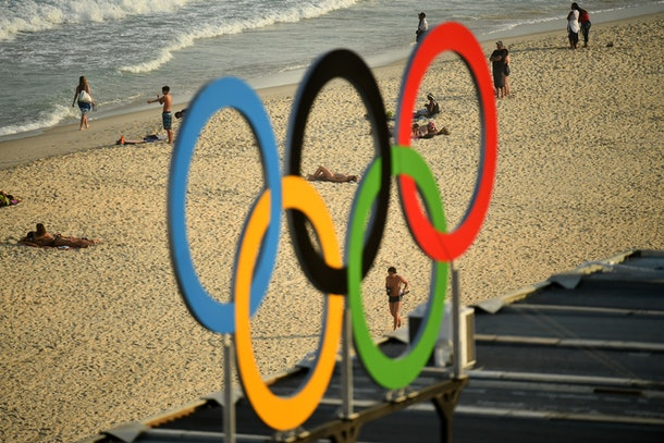 TOPSHOT - People are pictured walking along Copacaba beach through a set of Olympic rings, from during the men's beach volleyball qualifying match between Latvia and Cuba at the Beach Volley Arena in Rio de Janeiro on August 9, 2016, during the Rio 2016 Olympic Games. / AFP / Leon NEAL        (Photo credit should read LEON NEAL/AFP/Getty Images)