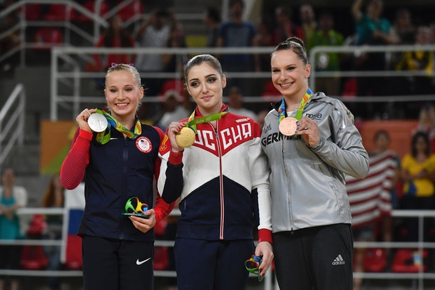 (L-R) US gymnast Madison Kocian, Russia's Aliya Mustafina and Germany's Sophie Scheder celebrate on the podium of the women's uneven bars event final of the Artistic Gymnastics at the Olympic Arena during the Rio 2016 Olympic Games in Rio de Janeiro on August 14, 2016. / AFP / Ben STANSALL        (Photo credit should read BEN STANSALL/AFP/Getty Images)