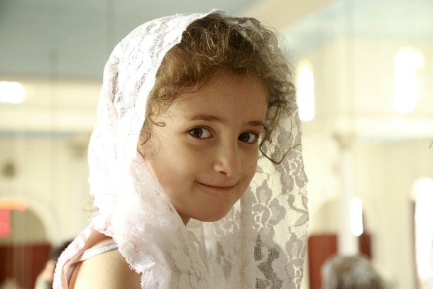 A Syrian Syriac Christian girl attends a mass marking the assumption of the Virgin Mary on August 15, 2016 at the Saint Mary's Syriac Orthodox Church in the northeastern city of Qamishli. / AFP / DELIL SOULEIMAN        (Photo credit should read DELIL SOULEIMAN/AFP/Getty Images)
