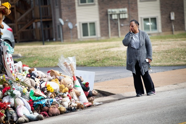 FERGUSON, MO - MARCH 14:  Mia Swisher wipes away a tear during a visit to a memorial to Michael Brown outside the Canfield Green apartments where he was shot and killed by a police officer last August on March 14, 2015 in Ferguson, Missouri.  The town of Ferguson has experienced many protests, which have often been violent, since Brown's death. On Wednesday evening two police officers were shot while they were securing the Ferguson police station during a protest.  (Photo by Scott Olson/Getty Images)