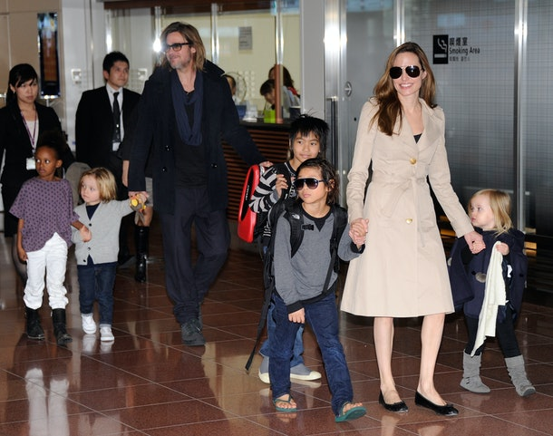 Accompanied by their children, US movie stars Brad Pitt and Angellina Jolie appear before photographers upon their arrival at Haneda Airport in Tokyo on November 8, 2011. Brad Pitt is here for the Japan premiere of his last film 'Moneyball'.   AFP PHOTO/Toru YAMANAKA (Photo credit should read TORU YAMANAKA/AFP/Getty Images)
