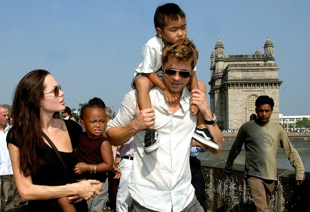 US actor Angelina Jolie (L) holds daughter Zahara as husband and actor Brad Pitt (C) carries son Maddox during a stroll on the seafront promenade at the historic Gateway of India, (R) outside their hotel in Mumbai, 12 November 2006. Jolie and Pitt are in India's financial hub - Mumbai to shoot for her film 'A Mighty Heart', based on the life of the slain Wall Street Journal reporter Daniel Pearl in which Jolie portrays Marianne - wife of Daniel Pearl.        (Photo credit should read STR/AFP/Getty Images)