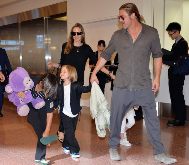 US film stars Brad Pitt (R) and Angelina Jolie (back C), accompanied by their children, arrive at Haneda International Airport in Tokyo on July 28, 2013.  Pitt is now here for the promotion of his latest movie 'World War Z'.     AFP PHOTO / Yoshikazu TSUNO        (Photo credit should read YOSHIKAZU TSUNO/AFP/Getty Images)