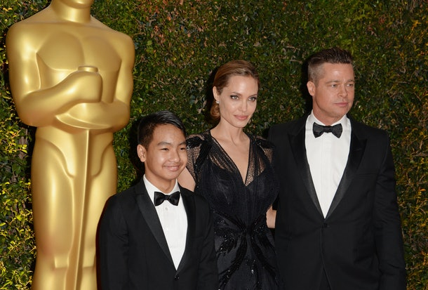 Actress Angelina Jolie, Maddox Jolie-Pitt (L) and actor Brad Pitt arrive for the 2013 Governors Awards, presented by the American Academy of Motion Picture Arts and Sciences (AMPAS), at the Grand Ballroom of the Hollywood and Highland Center in Hollywood, California, November 16, 2013.  AFP PHOTO / Robyn Beck        (Photo credit should read ROBYN BECK/AFP/Getty Images)