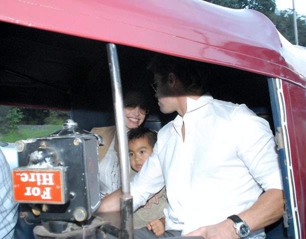 Pune, INDIA:  US actors Brad Pitt (R) and Angelina Jolie (L) sit with their son Maddox (C) inside an Indian auto rickshaw as they take a tour of Pune, some 200kms south of Mumbai, 08 October 2006.  The couple are expected to spend a month in India filming 'A Mighty Heart,' based on the book of the same name by Pearl's widow Mariane about her husband's abduction and murder by Islamic militants in Pakistan in 2002. Jolie plays Mariane while Dan Futterman plays Pearl.     AFP PHOTO/STR  (Photo credit should read STRDEL/AFP/Getty Images)