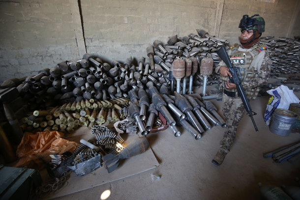 Iraqi soldiers and officers walk near weapons and ammunition that were collected after allied Iraqi forces retook the city of Fallujah from jihadists of the Islamic State (IS) group, on September 4, 2016 in Fallujah.  Iraq's security forces have for months been battling IS fighters in Anbar province, notching up key victories in provincial Ramadi and jihadist bastion Fallujah earlier this year.   / AFP / AHMAD AL-RUBAYE        (Photo credit should read AHMAD AL-RUBAYE/AFP/Getty Images)