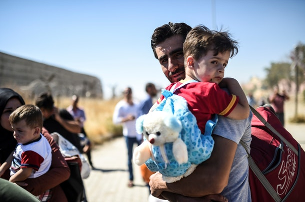 Syrian refugees walk on their way back to the Syrian city of Jarabulus  on September 7, 2016 at Karkamis crossing gate, in the southern region of Kilis. / AFP / BULENT KILIC        (Photo credit should read BULENT KILIC/AFP/Getty Images)