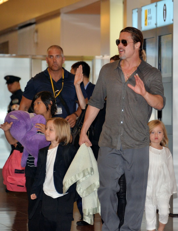US film stars Brad Pitt (R) smiles as he arrives with partner Angelina Jolie (hidden) and their children at Haneda International Airport in Tokyo on July 28, 2013.  Pitt is now here for the promotion of his latest movie 'World War Z'.     AFP PHOTO / Yoshikazu TSUNO        (Photo credit should read YOSHIKAZU TSUNO/AFP/Getty Images)