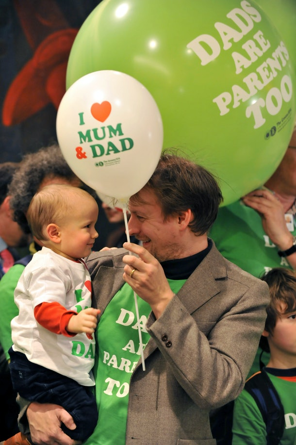 A child and a man smile during a demonstration by parents supporting the MEP green party's bid for fathers to obtain two weeks of fully paid paternity leave on February 23, 2010 outside a room where the Committee for gender equality and women's rights of the European Parliament is assembled at the European Parliament. AFP PHOTO GEORGES GOBET (Photo credit should read GEORGES GOBET/AFP/Getty Images)