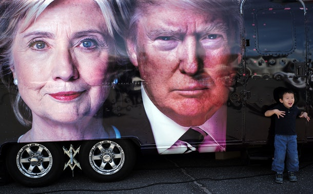 A boy gestures next to a backdrop of US Democratic presidential nominee Hillary Clinton and her Republican counterpart Donald Trump at the Hofstra University, in Hempstead, New York on September 26, 2016.  Hillary Clinton and Donald Trump prepared to square off Monday in their first presidential debate -- a keenly awaited clash that comes as they sit nearly neck and neck in the polls. / AFP / Jewel SAMAD        (Photo credit should read JEWEL SAMAD/AFP/Getty Images)