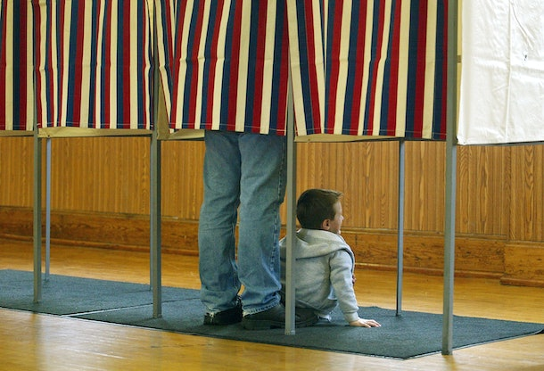 HAZEL GREEN, WI - NOVEMBER 2:  An unidentified voter casts his ballot as his son sits and waits to depart the voting booth at a polling place November 2, 2004 in Hazel Green, Wisconsin. Wisconsin is a swing state both presidential candidates hope to win.  (Photo by Tim Boyle/Getty Images)