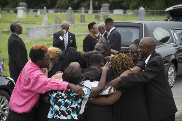 Gary L. Washington (C), son of Emanuel AME Church shooting victim Ethel Lance, is hugged by members of his family during his mother's burial at the Emanuel AME Church Cemetery in Charleston, South Carolina, June 25, 2015.    AFP PHOTO/JIM WATSON        (Photo credit should read JIM WATSON/AFP/Getty Images)