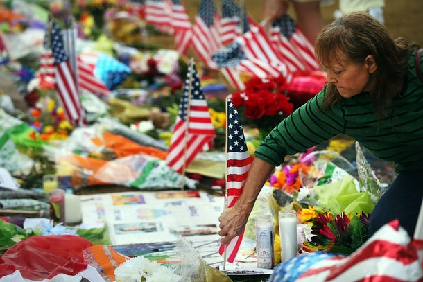 ORLANDO, FL - JUNE 16:  A woman places American flags at a memorial down the road from the Pulse nightclub on June 19, 2016 in Orlando, Florida. In what is being called the worst mass shooting in American history, Omar Mir Seddique Mateen killed 49 people at the popular gay nightclub early last Sunday. Fifty-three people were wounded in the attack which authorities and community leaders are still trying to come to terms with.  (Photo by Spencer Platt/Getty Images)