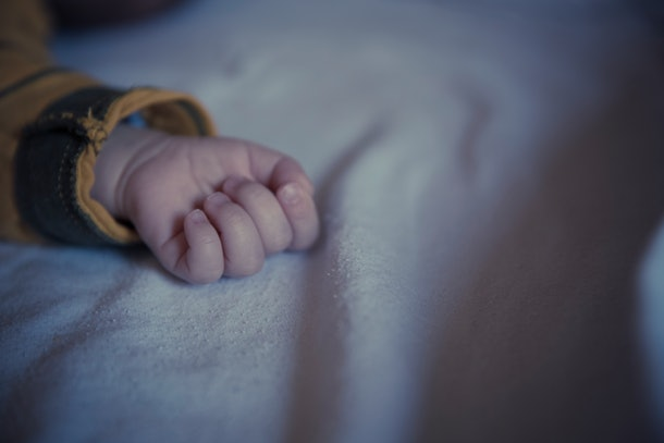 baby hand resting on bed