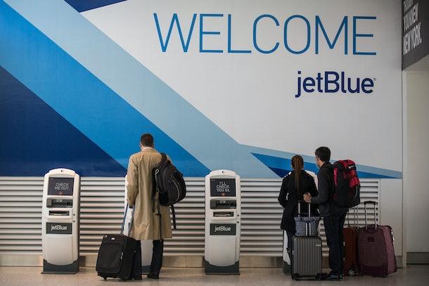 Travelers check in for flights using JetBlue kiosks.