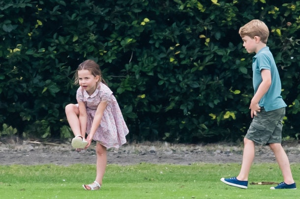 The royal kids are dressed up while playing outside.